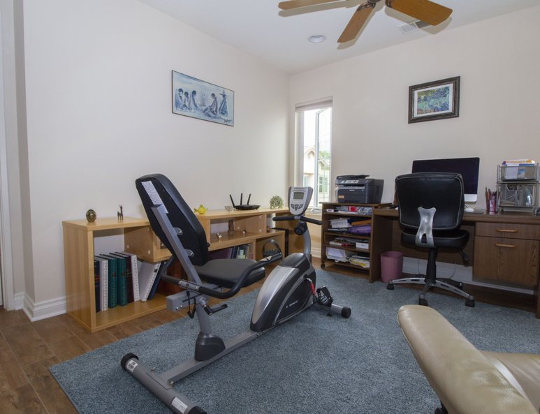 Open loft with newly installed windows, desk area and work-out equipment.