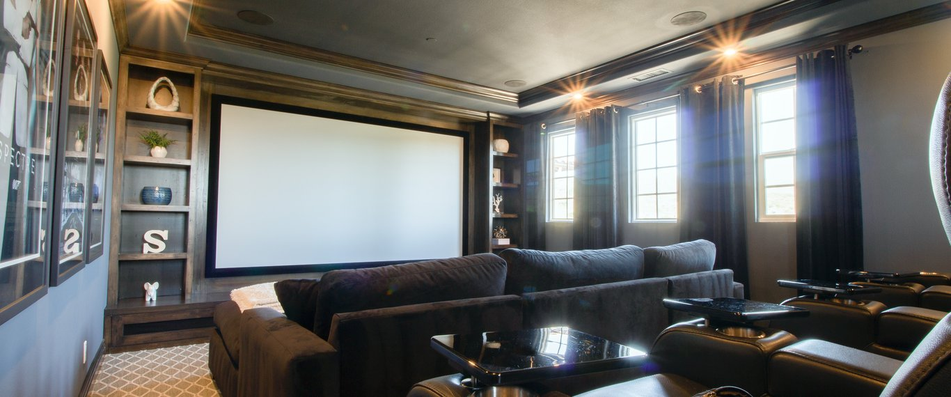 Home theatre with dark wood moulding and coffered ceiling