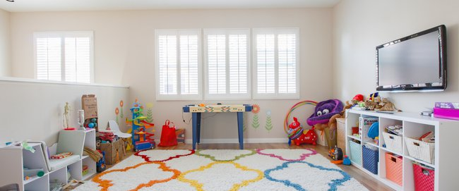 Open loft playroom with colorful rug, ponywall and multiple toys