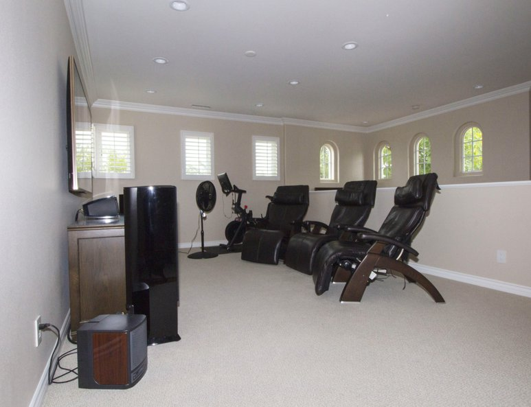 Family room with a sitting area, workout equipment and a ponywall with white wood baseboards and cap