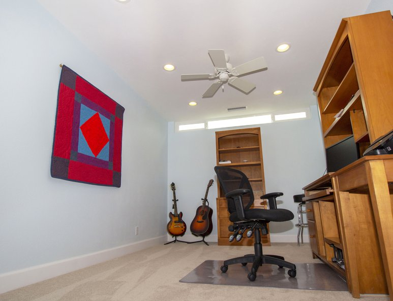 Open loft being utilized as a home office with a ceiling fan and recessed lighting.