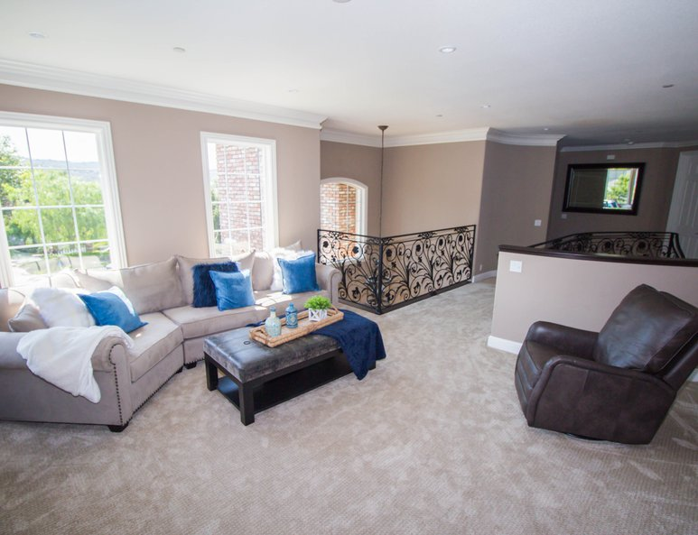 Large family room with ample lighting, wall-mounted television and plenty of seating