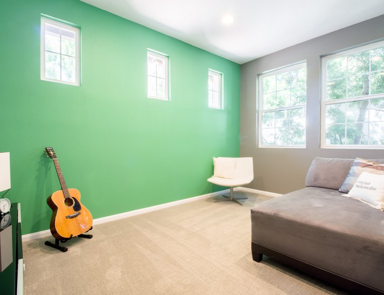 Open loft family room with lime green accent wall and ample lighting.